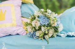 在一张床上的新娘花束在枕头中 库存图片
