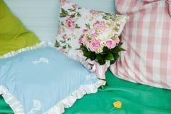 在一张床上的新娘花束在枕头中 免版税库存图片