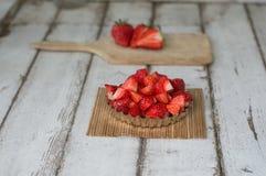 在一张木书桌上的切的草莓有一杯的牛奶 免版税库存照片