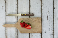 在一张木书桌上的切的草莓有刀子的 库存照片