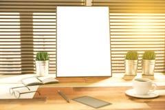 在一张木书桌上的空白的画框在日落 库存照片