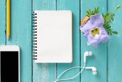 在一张木书桌上的顶视图有智能手机的,笔记本,铅笔和 库存照片