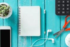 在一张木书桌上的顶视图有智能手机的,笔记本,铅笔和 库存图片