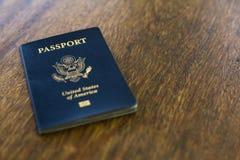 在一张木书桌顶部的一本蓝色美国护照 库存图片