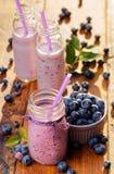 在一张木土气桌上的蓝莓圆滑的人 免版税图库摄影