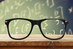 在一张木土气桌上的行家玻璃在有算术惯例和演算的前面黑板 被过滤的葡萄酒 库存照片