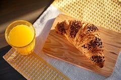在一张木板和洗碗布的新鲜的新月形面包与一个杯子橙汁 在一张黑暗的木桌上的新近地被烘烤的新月形面包 图库摄影