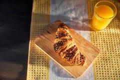 在一张木板和洗碗布的新鲜的新月形面包与一个杯子橙汁 在一张黑暗的木桌上的新近地被烘烤的新月形面包 免版税库存照片