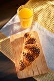在一张木板和洗碗布的新鲜的新月形面包与一个杯子橙汁 在一张黑暗的木桌上的新近地被烘烤的新月形面包 免版税库存图片