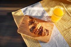 在一张木板和洗碗布的新鲜的新月形面包与一个杯子橙汁 在一张黑暗的木桌上的新近地被烘烤的新月形面包 库存照片