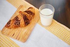 在一张木板和洗碗布的新鲜的新月形面包与一个杯子牛奶 在一张黑暗的木桌上的新近地被烘烤的新月形面包 库存照片