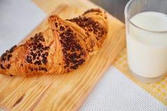 在一张木板和洗碗布的新鲜的新月形面包与一个杯子牛奶 在一张黑暗的木桌上的新近地被烘烤的新月形面包 免版税库存图片