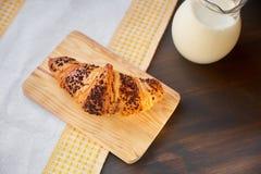 在一张木板和洗碗布的新鲜的新月形面包与一个蒸馏瓶牛奶 在一张黑暗的木桌上的新近地被烘烤的新月形面包 库存照片
