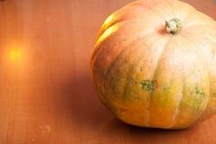 在一张木桌上的一个橙色南瓜 图库摄影