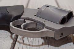 在一张木桌上的一把不锈的左轮手枪 图库摄影