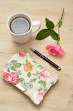 在一张木桌上的一本闭合的用花装饰的日志与桃红色上升了 库存图片
