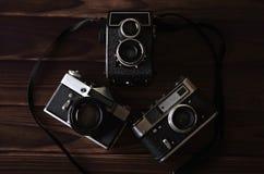 在一张木桌上的三台老葡萄酒照相机 库存照片