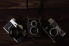 在一张木桌上的三台老葡萄酒照相机 库存图片