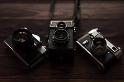 在一张木桌上的三台老葡萄酒照相机 免版税库存照片