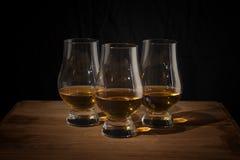在一张木桌上的三块威士忌酒玻璃 免版税库存照片