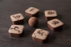 在一张木桌上的不同的巧克力糖 免版税库存图片