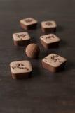 在一张木桌上的不同的巧克力糖 免版税库存照片