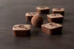 在一张木桌上的不同的巧克力糖 图库摄影