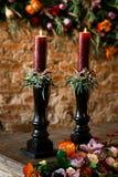 在一张木桌上的两个红色蜡烛 库存照片