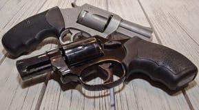 在一张木桌上的两把不同左轮手枪 免版税库存图片