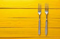 在一张木桌上的两把古色古香的叉子以黄色 顶视图 库存照片