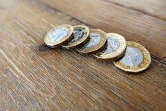 在一张木桌上的五个英国英国1英镑硬币 库存图片