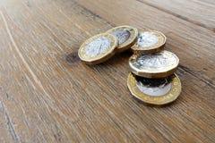在一张木桌上的五个英国英国1英镑硬币 免版税库存图片