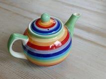 在一张木桌上的五颜六色的茶壶 免版税库存图片