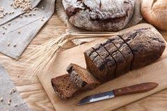 在一张木桌上的切的黑面包 免版税库存图片