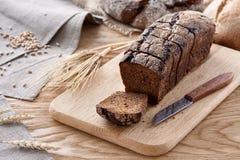在一张木桌上的切的黑面包 免版税库存照片