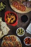 在一张木桌上的各种各样的塔帕纤维布盘乳酪和酒 免版税库存照片