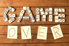 在一张木桌上的多米诺 题字比赛结束 库存图片