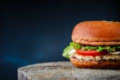 在一张木桌上的开胃自创汉堡在深蓝背景 免版税库存图片