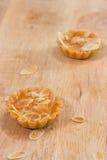 在一张木桌上的微型乳酪蛋糕桃子 免版税图库摄影