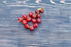 在一张木桌上的成熟水多的樱桃 免版税库存图片