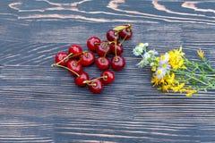 在一张木桌上的成熟水多的樱桃 免版税库存照片