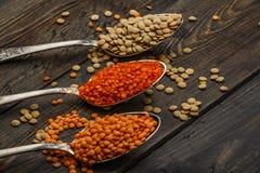 在一张木桌上的扁豆种子在生来有福 扁豆红色和绿色食物添加剂种子  豆类fa的有用的扁豆 图库摄影