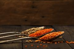 在一张木桌上的扁豆种子在生来有福 扁豆红色和绿色食物添加剂种子  豆类fa的有用的扁豆 库存照片