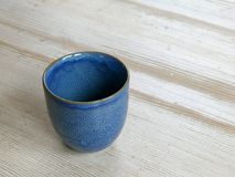 在一张木桌上的手工制造蓝色咖啡杯 免版税库存图片