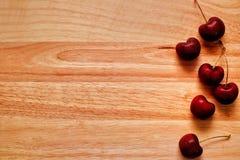 在一张木桌上的新鲜的樱桃 免版税库存图片