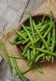在一张木桌上的新鲜的被采摘的青豆 库存照片