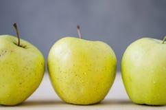 在一张木桌上的新鲜的黄色苹果 免版税库存照片
