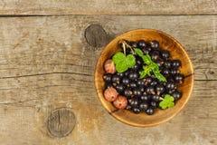 在一张木桌上的新鲜的黑醋栗 健康果子,有很多维生素和抗氧剂 健康的食物 免版税图库摄影