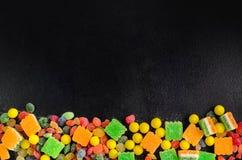 在一张木桌上的明亮地色的糖果与copyspace 免版税库存照片