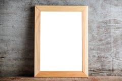 在一张木桌上的木制框架在灰色墙壁上 模板布局f 免版税库存照片
